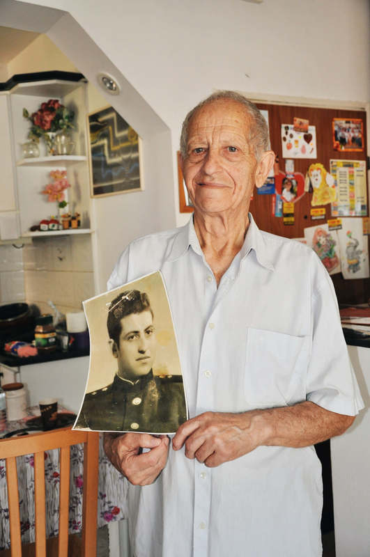 Holocaust survivor holding a picture of his younger self